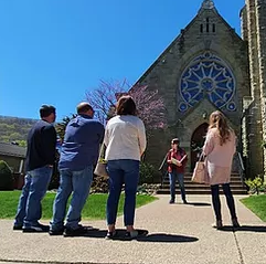 A group of people listen to a tour guide outside a historic building